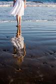 Kvinna promenerar på stranden — Stockfoto