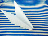 Paper airplane on striped fabric — Stock Photo