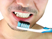 Closeup of man, brushing teeth with a blue tooth brush — Stock Photo
