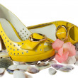 Pair of yellow shoes and seashells isolated on white - Stock Photo
