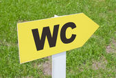 WC sign pointing direction on a green grass — Stock Photo