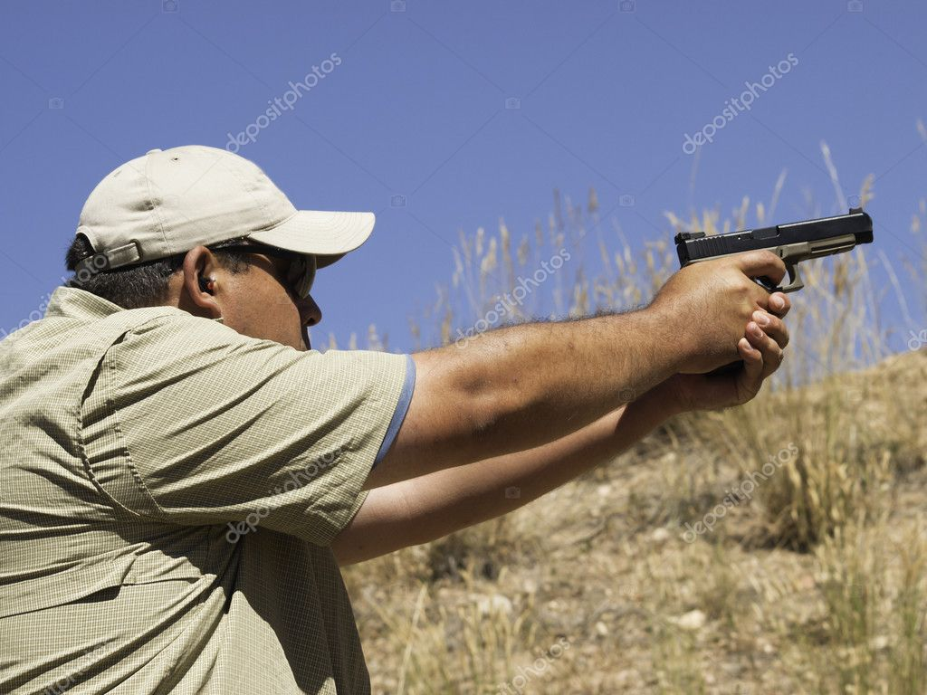 Man practicing target shooring.  Stock Photo #6729821