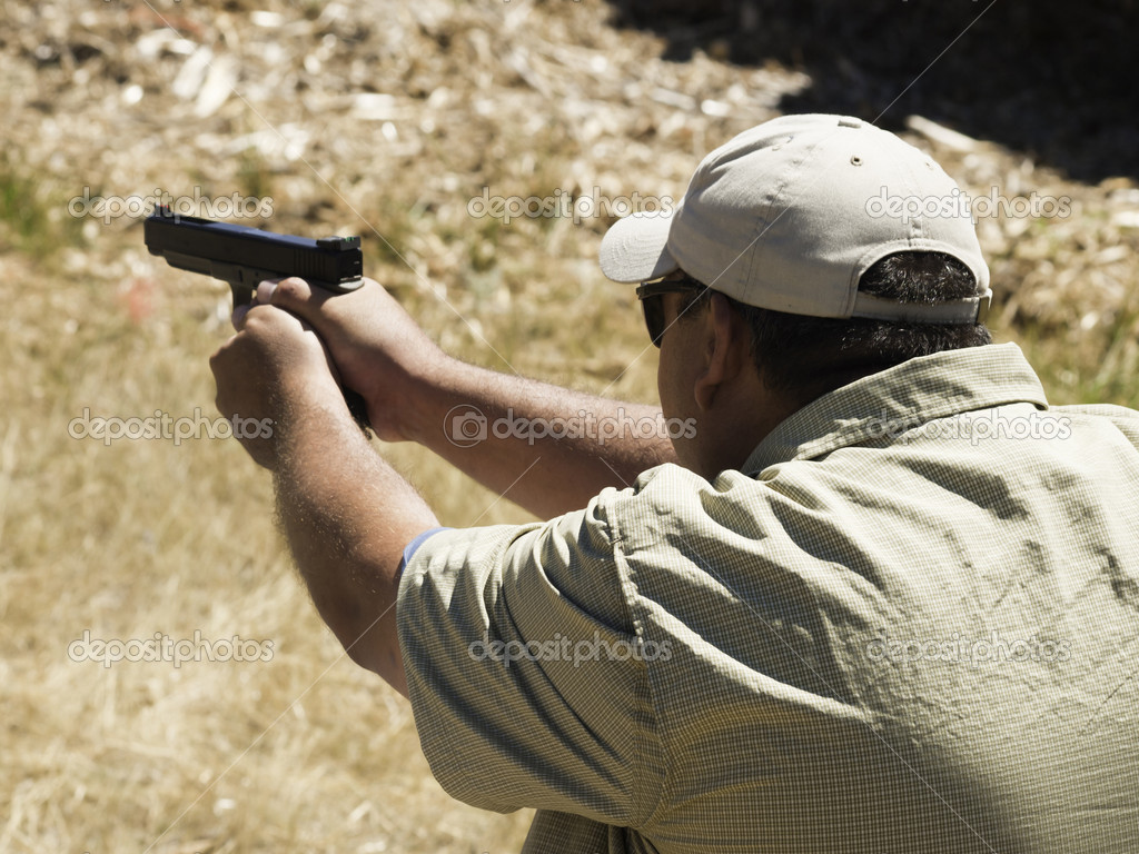Man practicing target shooring.  Stock Photo #6729929