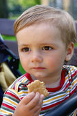 Walking boy eats biscuits — Stock Photo