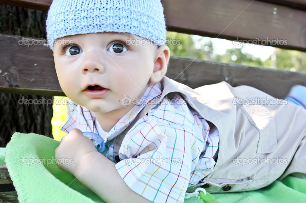 Adorable  baby boy on on the bench in the park  Stock Photo #6736565