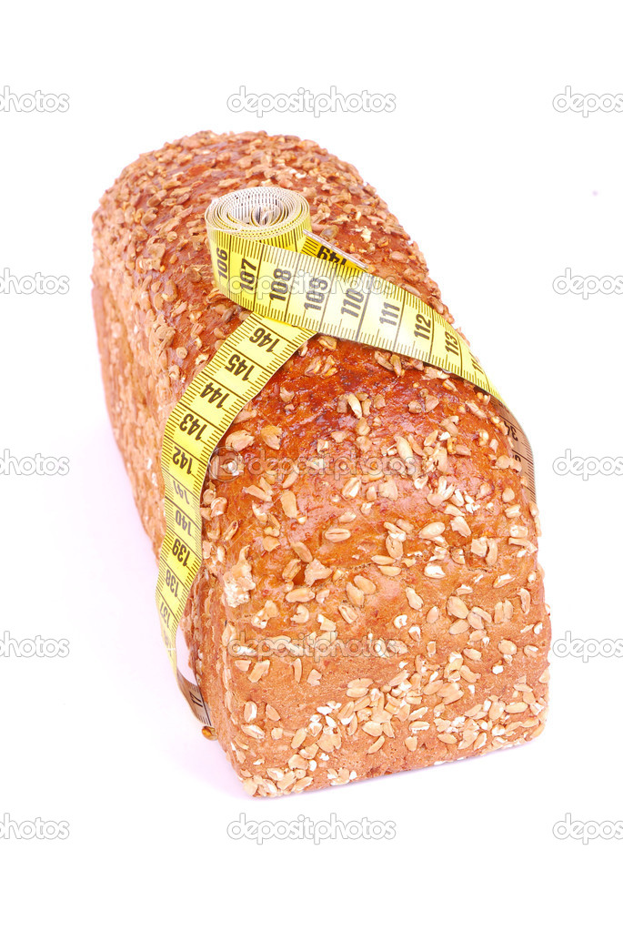 A loaf of whole grain healthy bread topped with seeds and with measurement tape around. Image isolated on white studio background.  Stock Photo #6448229