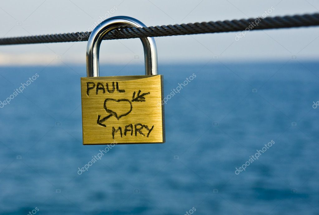 Padlock hanging on a cable bridge to the beach as a symbol of love forever — Stock Photo #6130512