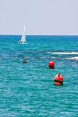 Small sailboat swims past buoy in Mediterranean sea — Stock Photo