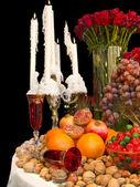 Заказать стол свечи, фрукты, орехи и цветы — Стоковое фото