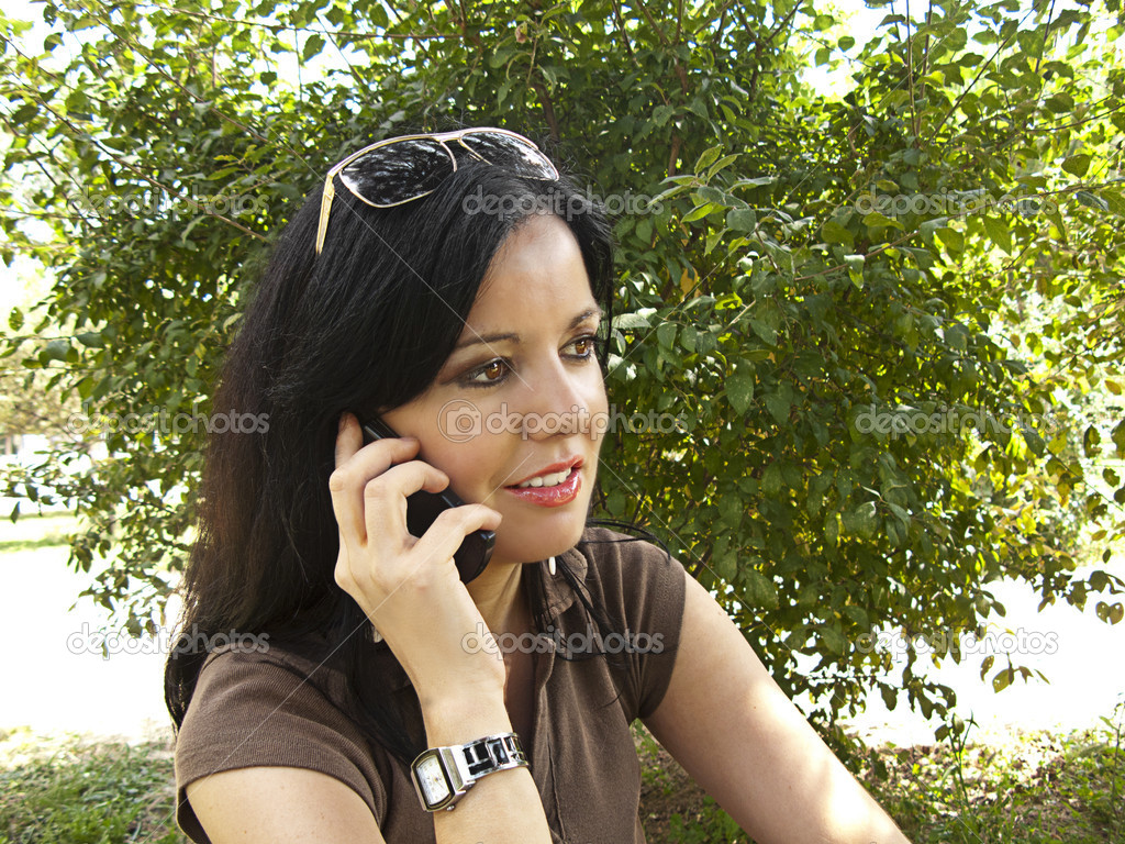 Beautiful young brunette woman talking on her mobile phone at the garden  Stock Photo #6421927