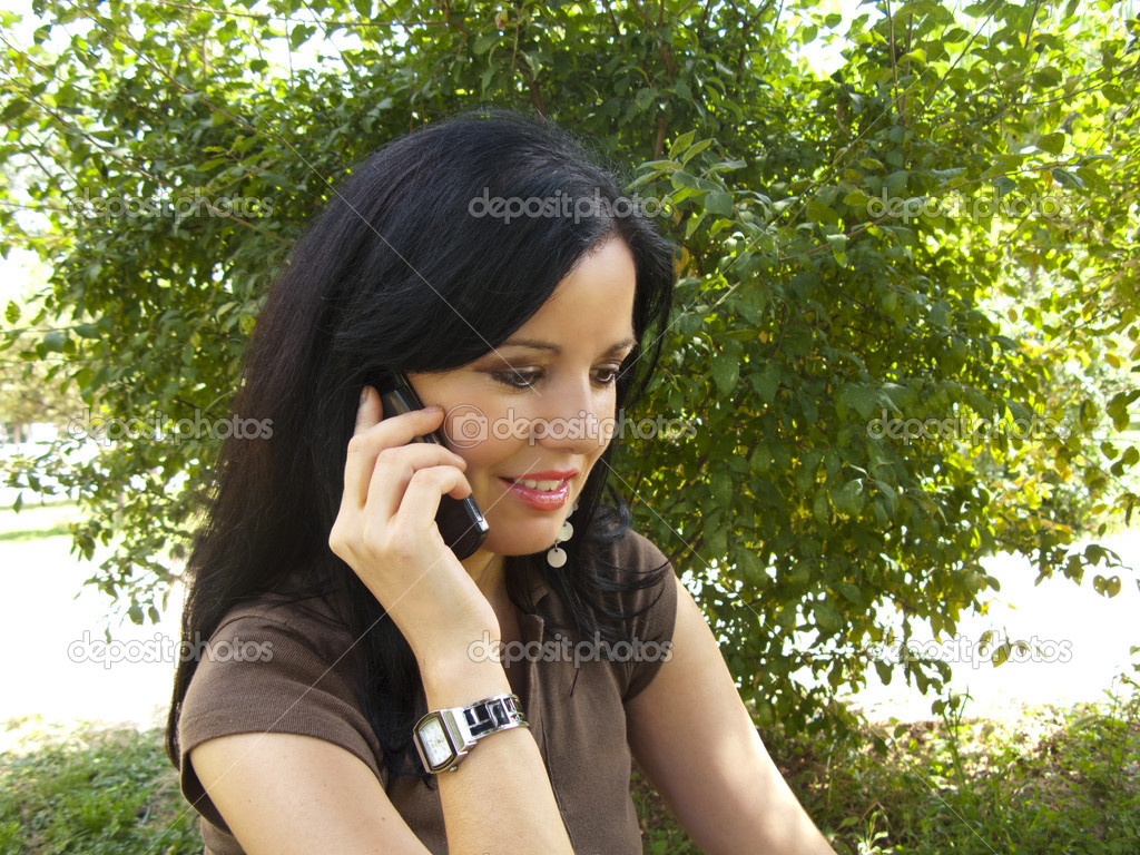 Beautiful young brunette woman talking on her mobile phone at the garden  Stock Photo #6421933