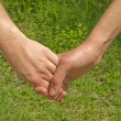 Two hands over green nature background. Love and friendship concept — Stock Photo