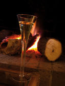 A cup of champagne near fireplace, at home in winter. Warm and romantic atm — Stock Photo