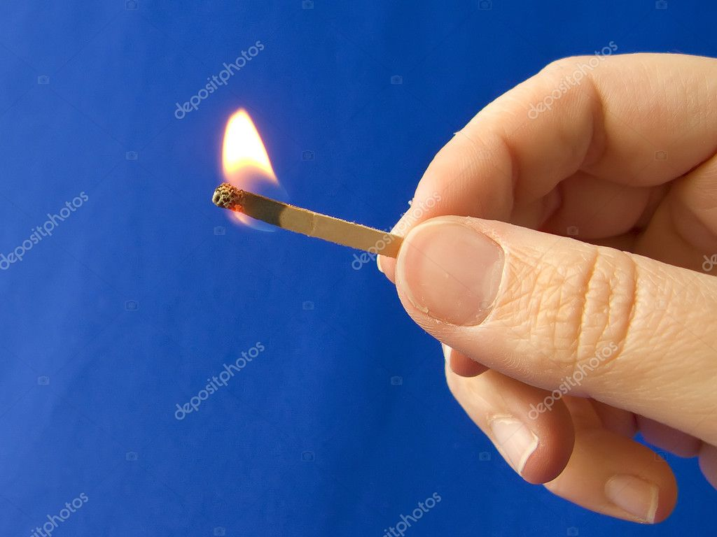A hand holding a fired matchstick  Stock Photo #6729215