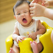 6 month old Asian baby girl having a haircut — Stock Photo #6319656