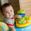 6 month old Asian baby girl plays sitting in a walker — Stock Photo #6362003