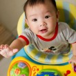 6 month old Asian baby girl plays sitting in a walker — Stok fotoğraf