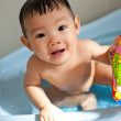 8 month old Asian baby girl having fun playing with water during her bath — Stock Photo #6362090