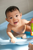 8 month old Asian baby girl having fun playing with water during her bath — Stock Photo