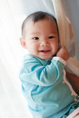 7 month old Asian baby girl smiling and holding on to a curtain — Stock Photo