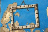 Antiguo vacío marco colgando de un azul de la pared rota — Foto de Stock