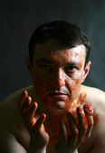 Man soiled with a red paint — Stock Photo