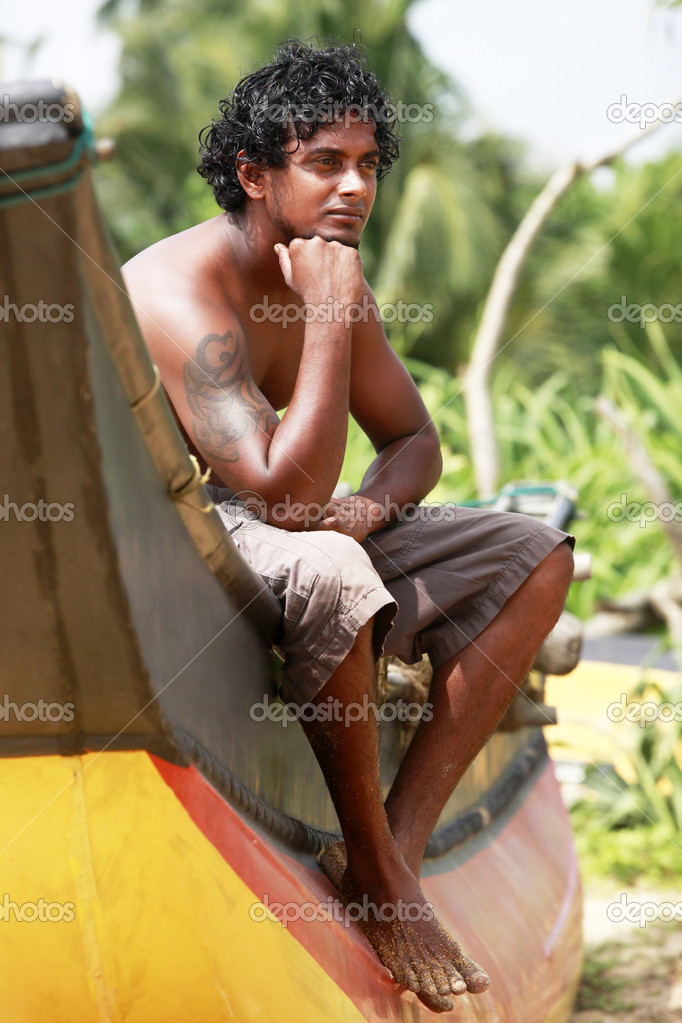 The young man sitting by a boat. Sri Lanka — Stock Photo #6172592