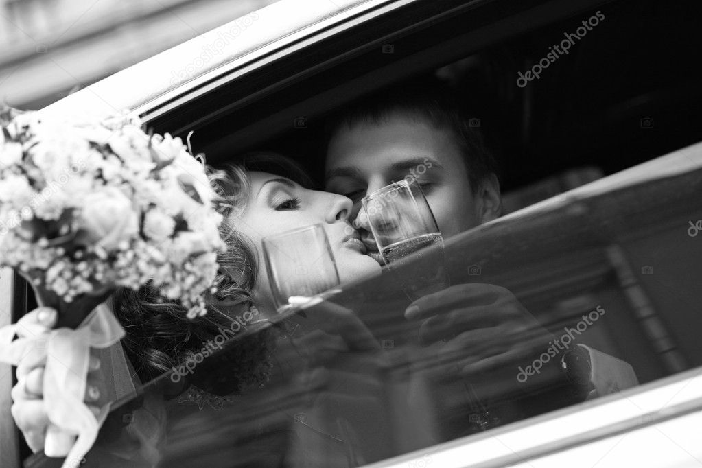 Newly-married couple in car with champagne — Photo #6202579