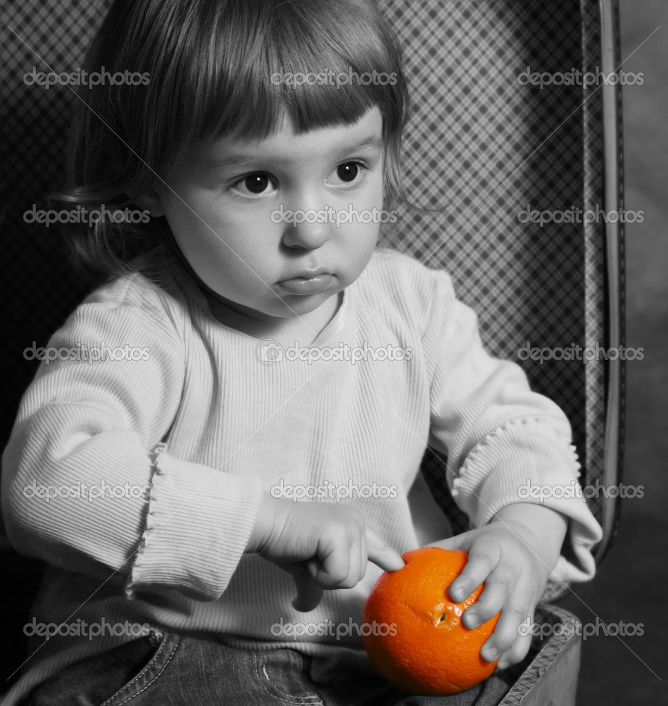 The little girl sits in a suitcase with orange — Stock Photo #6247998