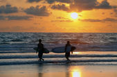 Surfers at red sunset — Stock Photo