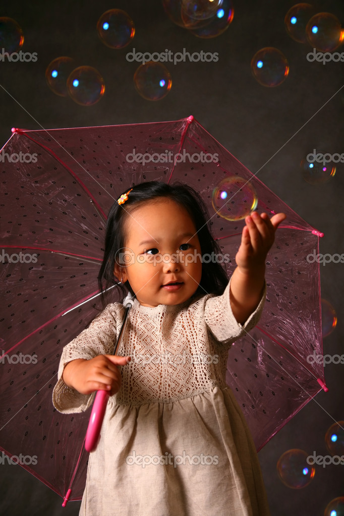 The small Korean girl with a umbrella and soap bubbles  Stock Photo #6613168