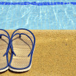 Women's sandals on the feet of the pool — Stock Photo