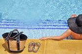 Mulheres com pamela numa posição relaxada na piscina com a bolsa e sandálias — Foto Stock