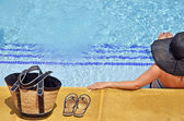 Women with pamela in a relaxed position in the pool with bag and sandals — Foto Stock
