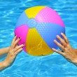 Hands of mother and daughter playing with Multi Colored Beach ball in swimm — Stock Photo