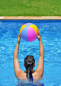 Woman exercising in the pool with beach ball — Stock Photo
