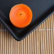 Stock Photo: Orange candle in black dish on bamboo
