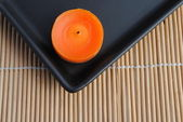 Orange candle in black dish on bamboo — Stock Photo