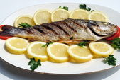 Grill cooked fish with lemon slices — Stock Photo