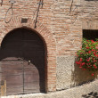 Sarnano (Macerata, Marches, Italy) - Old house with red flowers — Stock Photo