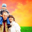 Happy family portrait outdoors smiling with a blue sky — Stock Photo