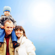 Happy family portrait outdoors smiling with a blue sky - Lizenzfreies Foto