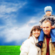 Happy family portrait outdoors smiling with a blue sky — Stock Photo #6352209