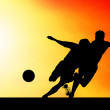 Silhouettes of footballers on the sunset sky — ストック写真
