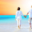 Royalty-Free Stock Photo: Rear view of a couple walking on the beach, holding hands.