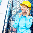 Stock Photo: Young architect-woman wearing a protective helmet standing on th