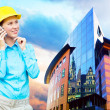 Stock Photo: Young architect-womwearing protective helmet standing on th