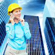 Young architect-woman wearing a protective helmet standing on th — Stock Photo #6352643