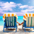 Rear view of a couple on a deck chair relaxing on the beach — Stock Photo #6352710