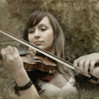 Beautiful female violinist playing violin on the grunge backgrou - Stock Photo